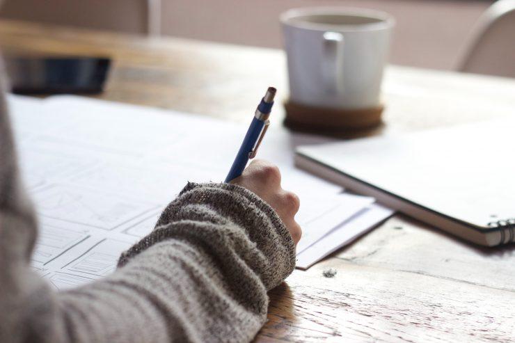 Eine Person die auf einem braunen Tisch schreibt. Person writing on brown wooden table near white ceramic mug.
